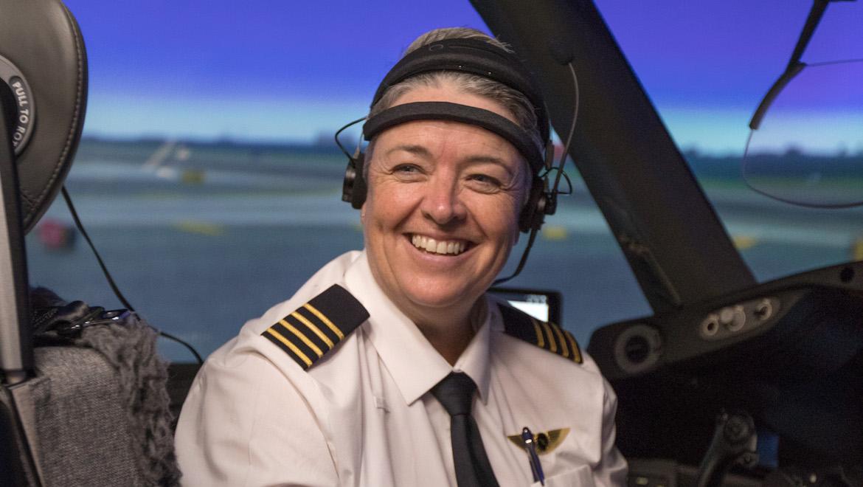 Captain Lisa Norman in the flight simulator wearing the electroencephalogram brain monitoring equipment.
